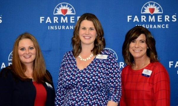 Agent standing with two women in front of a Farmers Insurance backdrop
