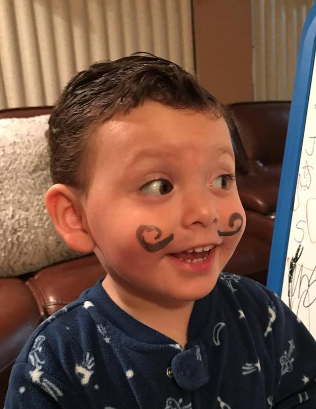Photo of a young child with a comical mustache drawn on his face.