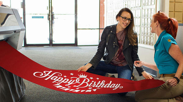 Employee and customer inspecting red birthday banner with white text