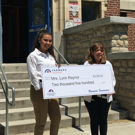two people holding large check on steps of school