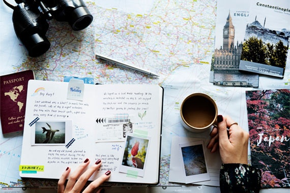 person drinking a cup of coffee looking at maps, pictures and a passport as they plan a trip