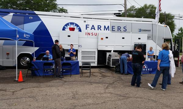 A large Farmers trailer is parked outside with many people surrounding it