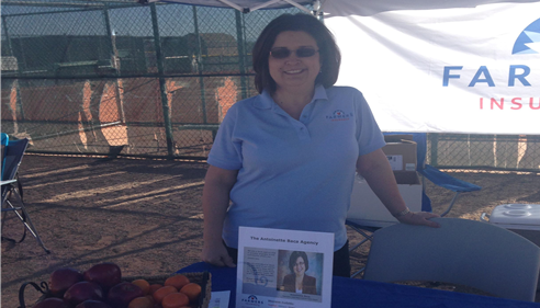 Agent Antoinette Baca standing with a Farmers Insurance promotional table inside of a batting cage