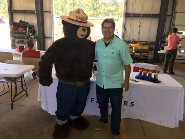 Man posing with Smokey the Bear