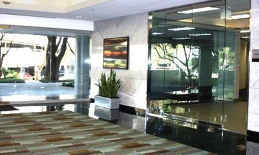Lobby of office building, partially with floor to ceiling mirrors and partially with ceramic walls. wide earth tone rug covering floor.