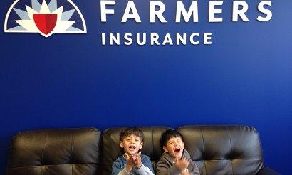 2 children in front of a farmers sign