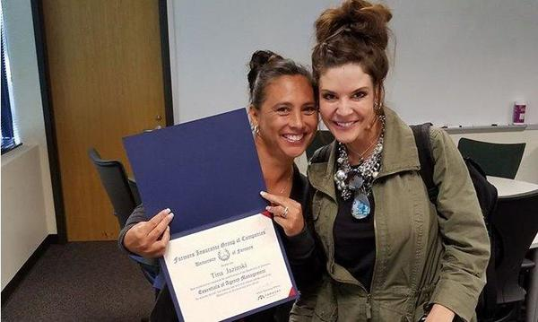 Agent Tina with female friend displaying diploma from University of Farmers.