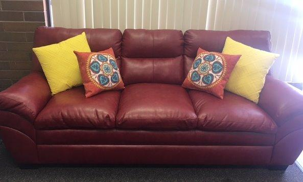 Red leather couch with yellow pillows