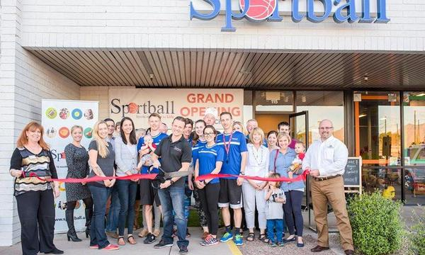 Bruce cuts a ribbon with oversized scissors in front of Sportball Scottsdale