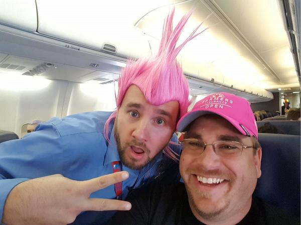 Guy with pink mohawk and agent on airplane smiling and guy with pink mohawk giving peace sign.