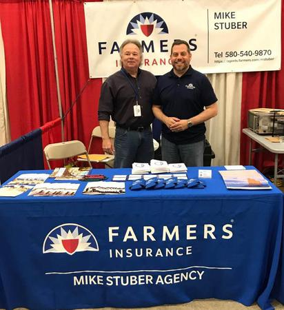 Two men working at a Farmers® Insurance booth.