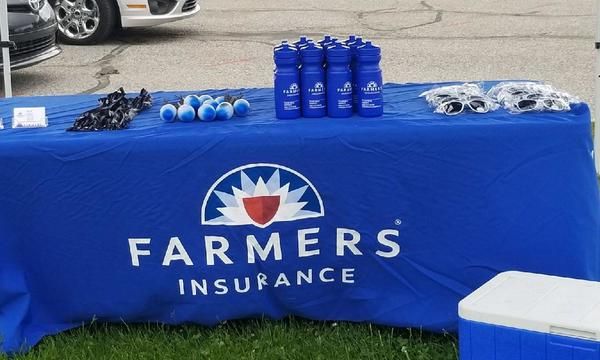 Farmers booth with water bottles and accessories.