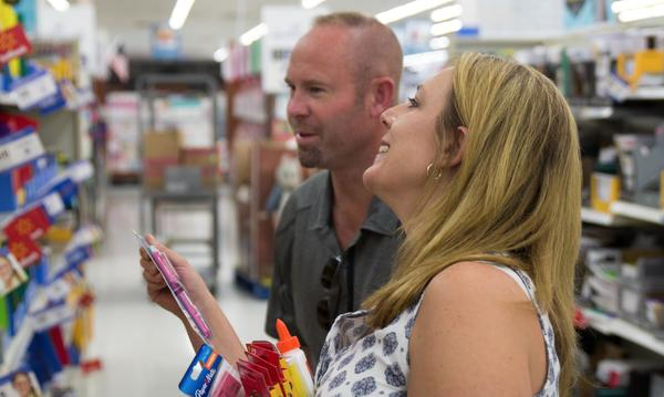 Agent Danielle shopping with male staff member for school supplies for back to school drive.