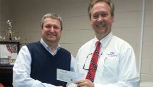 Agent Mark handing a check to member of the Walton High Athletics.