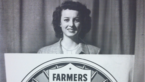 1950's picture of Farmers® lady holding a sign.