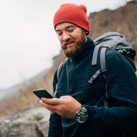 A bearded hiker checks their phone