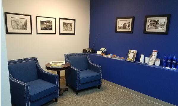 A room with blue walls and furniture inside of an office building.