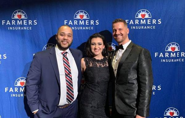 Two men and a woman at a Farmers wall dressed formally