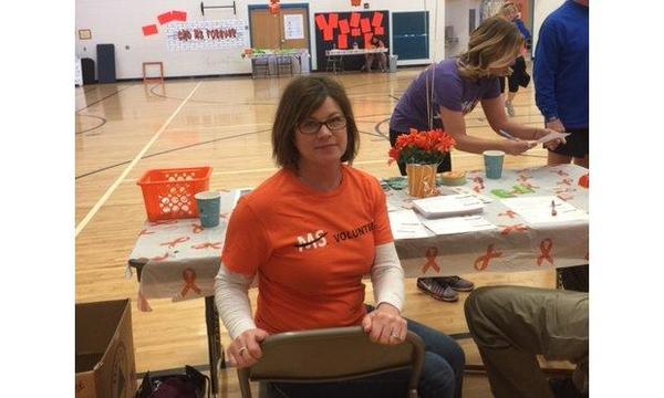 Agent Robin Snow sitting at a table as a volunteer for an annual MS walk.