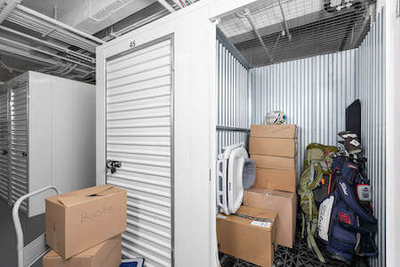 Storage unit packed with golf clubs, hiking gear, baby stuff, decorations, books, a guitar and lots of boxes!