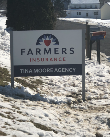 Photo of the Farmers Insurance sign for the Tina Moore Agency, next to the road in snowy grass.