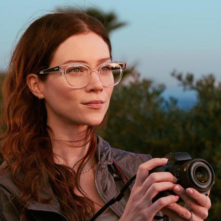 Woman holding a camera while wearing LensCrafters eyeglasses