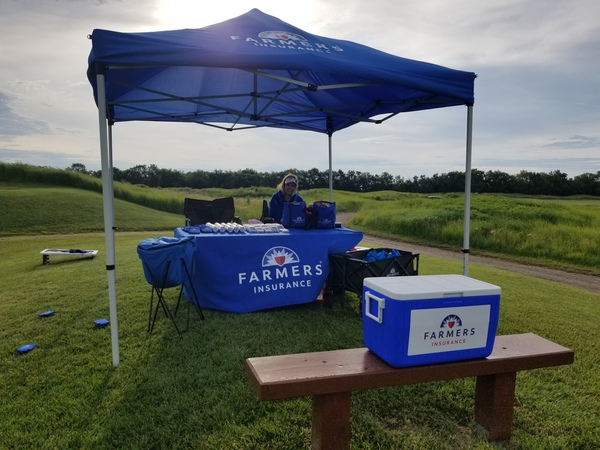 Photo of a Farmers Insurance table under a blue Farmers Insurance tent. Also featuring a blue cooler on a bench.