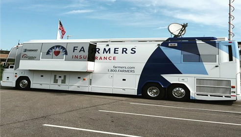 Large bus painted with the Farmers logo in a parking lot