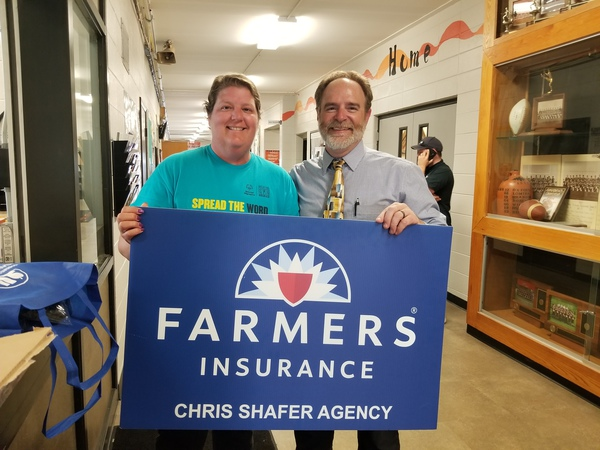 Two people holding a Farmers Insurance sign.