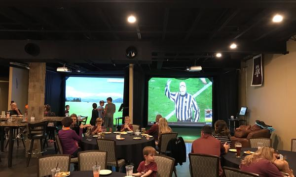 A group of people in a sports bar, watching football on two large TVs.