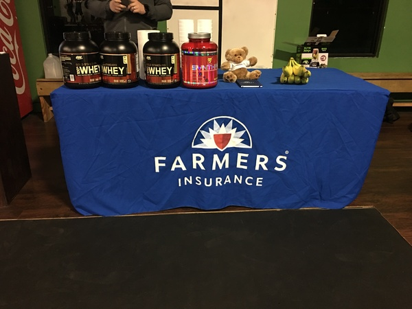 Tubs of protein powder on a table with the Farmers logo on it