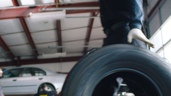 A Meineke mechanic rolls a tire towards a silver car that waits in the background.
