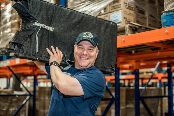 picture of man holding folding chairs over his shoulders while smiling.