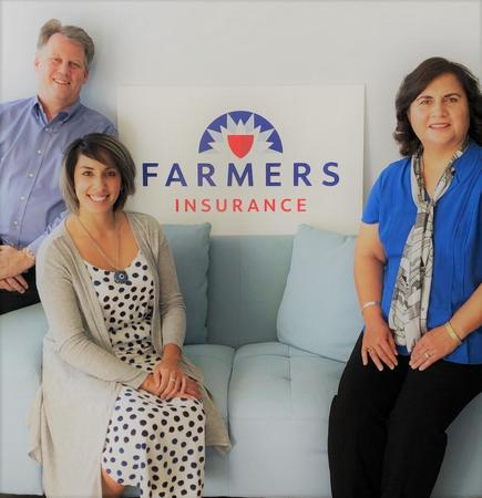 Group of three people posing on a light blue couch, in front of the Farmers Insurance logo.