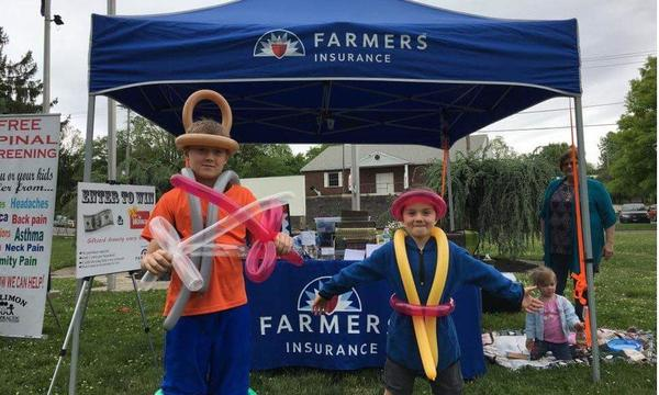 two young boys wearing balloons in front of a Farmers Booth