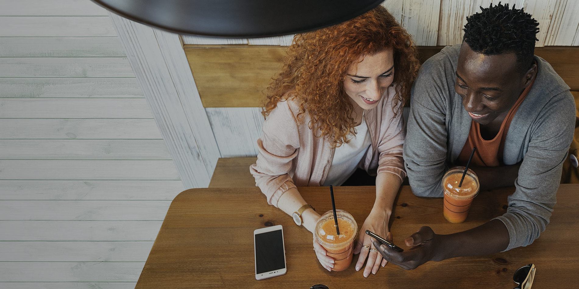 Photo of a young couple in a coffee shop smiling at a Altice Mobile connected smart phone