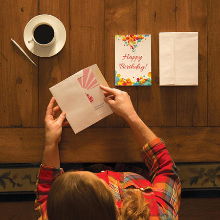 woman writing happy birthday card on table