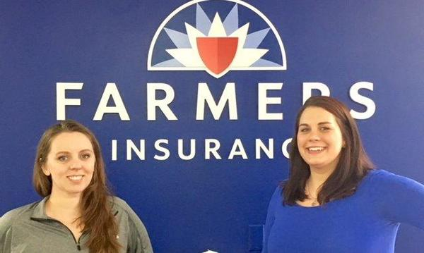 The agency pose in front of a Farmers Insurance logo