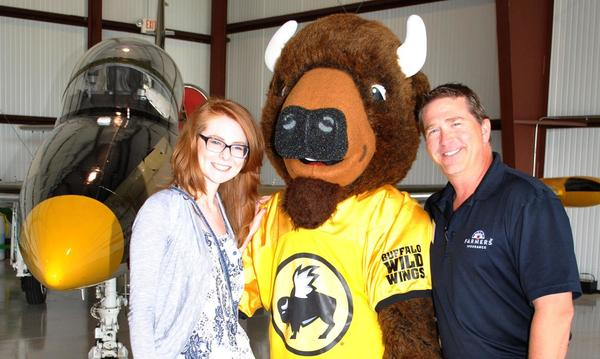 Two people pose with a large mascot of a bison
