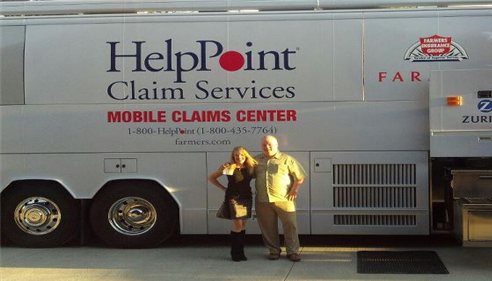Isabelle poses in front of the Help Point Claims Services bus