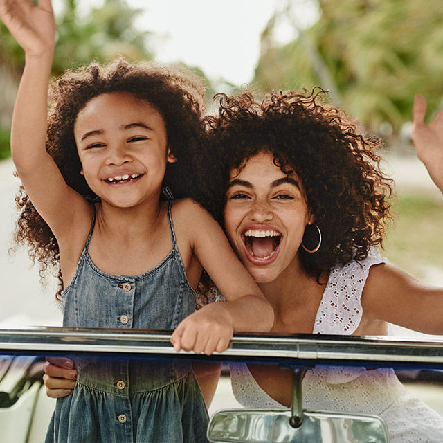 Woman and child waving inside a car.