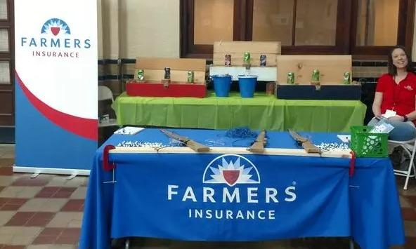 A blue Farmers Insurance promotional table for the Paul Persico Agency