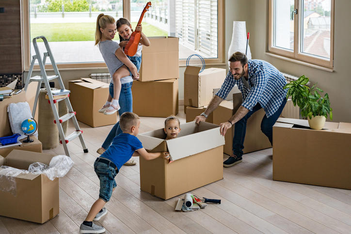 Family having fun with moving boxes while packing
