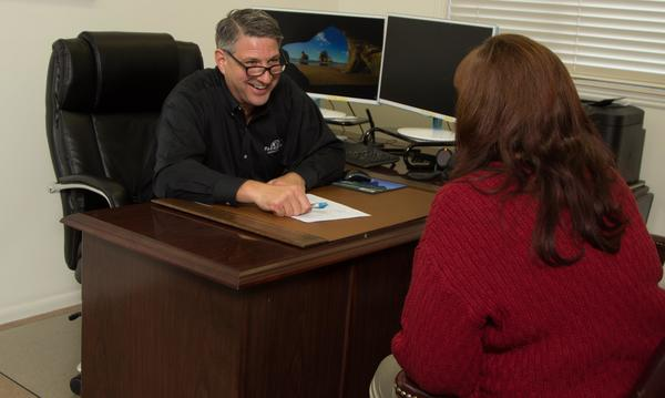 Agent sitting behind a desk smiling and talking with customers