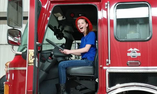 Agency staff member Ainsley inside of a firetruck at the Carlinville Fire Department Open House.