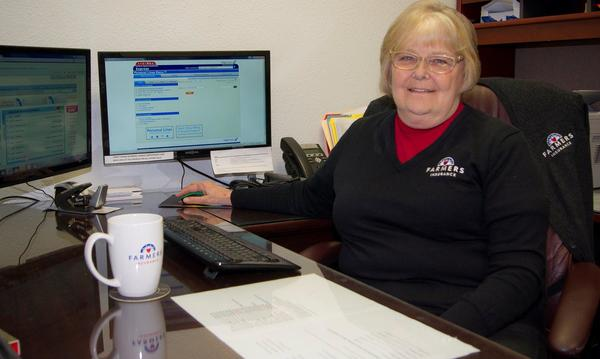 Staff member sitting and smiling at desk in Farmers branded sweater.