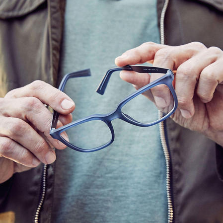 Man holding blue prescription eyeglasses