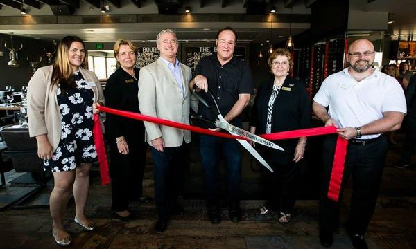 Bruce cuts a ribbon with oversized scissors in front of Bourbon and Bones