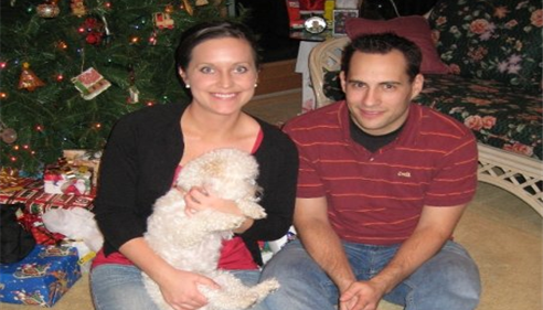 Agent and man sitting beneath a Christmas tree, holding a white dog