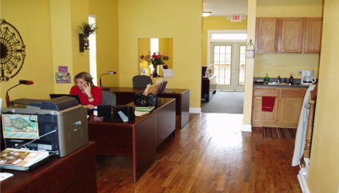 View from inside the office with yellow walls and a wooden desk with trinkets.